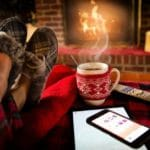 Person sitting by a fire place with a cup of coffee