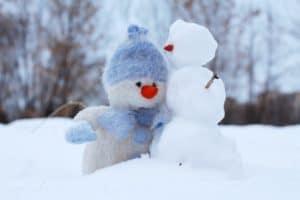 Stuffed snowman next to a real snowman