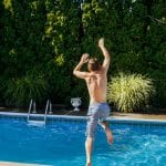 child jumping into a backyard pool