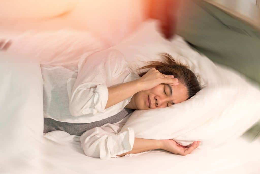 A person laying in bed and holding their head in discomfort