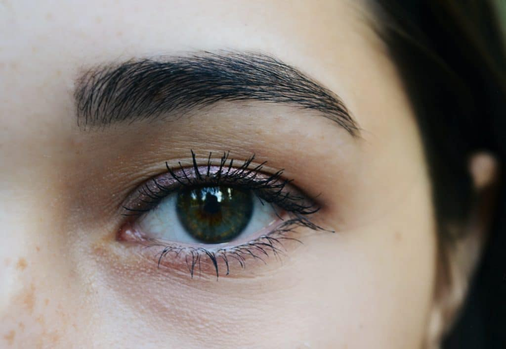 Up close shot of a light skinned woman with brown eye brows and hazel eyes.
