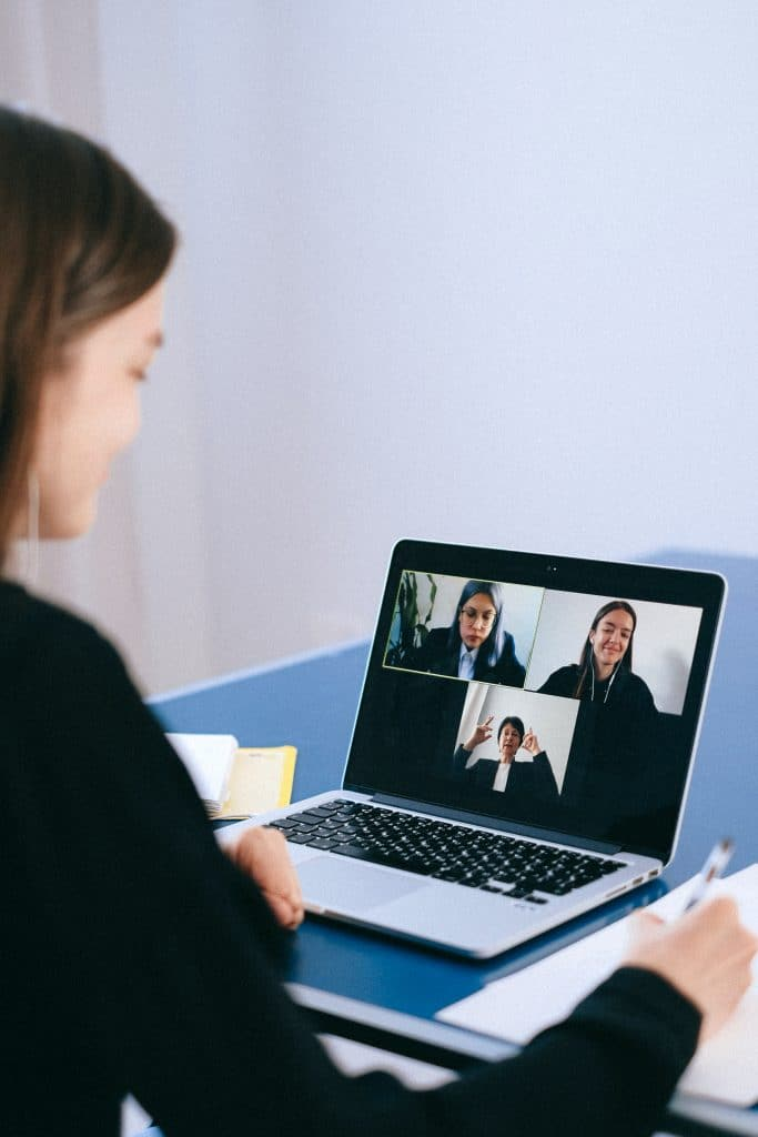 three coworkers displayed on a video call with a woman looking at the computer