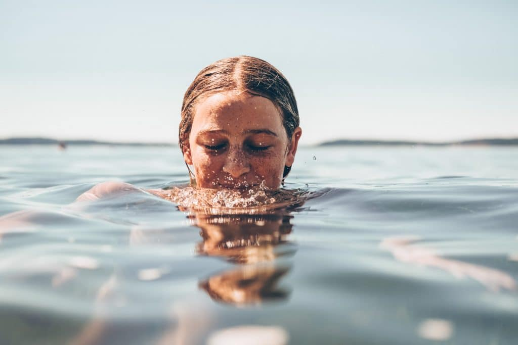 a woman in water with her face halfway under the water