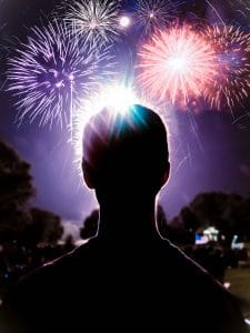 A silhouette of a person with fireworks booming in front of them