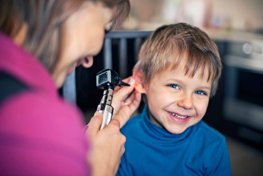 A young boy is getting his ears checked by a female doctor