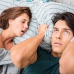 Woman snoring, man covering his ears