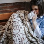Woman with allergy symptoms resting on couch.